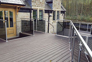 An outside deck with sunken hot tub, walkway & glass hand railing. Designed, supplied & installed by ASH Construction Ltd.